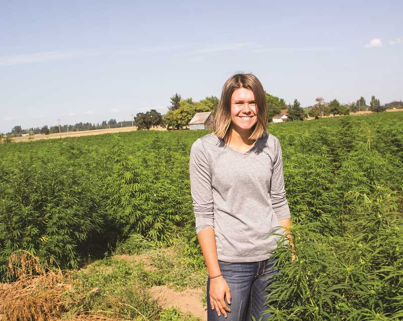 INDEPENDENT PHOTO: JULIA COMNES - Emily Iverson stands among the industrial hemp grown at her family's farm. The hemp they grow looks identical to marijuana but contains only trace amounts of THC, the psychoactive compound that causes marijuana users to get high.
