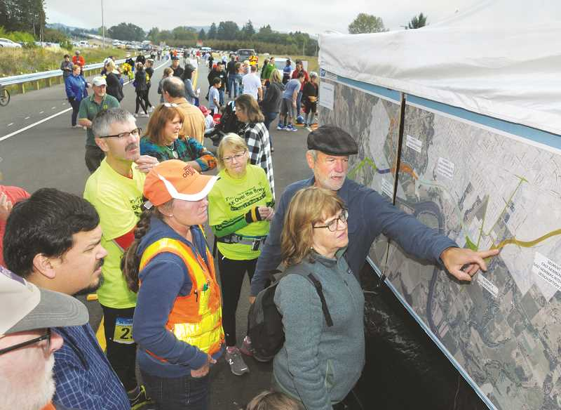 GARY ALLEN - ODOT Senior Engineering Geologist Kaie Castelli (in orange) talks about the route of the bypass before a large display erected on the thoroughfare Saturday morning.