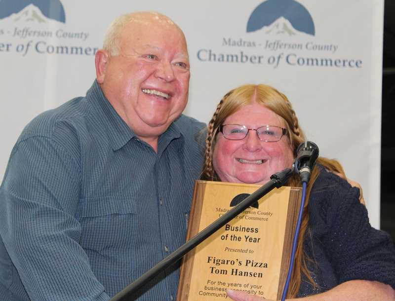 HOLLY M. GILL - Tom Hansen, the former owner of Figaro's in Madras, hugs longtime employee Susan Shockey afte he is honored with the Business of the Year award at the annual Chamber of Commerce Awards Banquet.