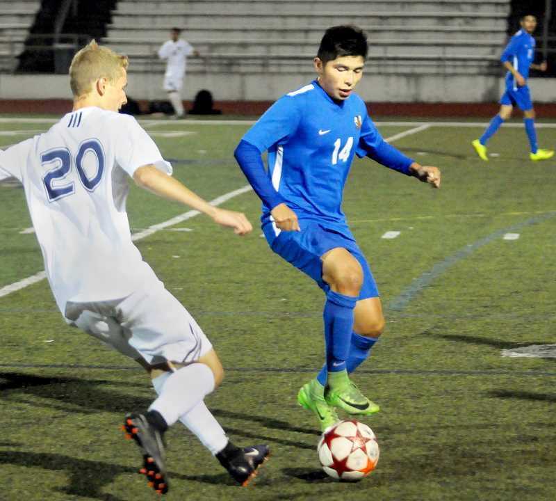 SETH GORDON - Newberg senior midfielder Alan Rodriguez looks to outmaneuver an opponent for the ball Sept. 21 during the Tigers' 0-1 road loss at Wilsonville. The Tigers bounced back with a 3-0 home win over Lincoln on Monday.
