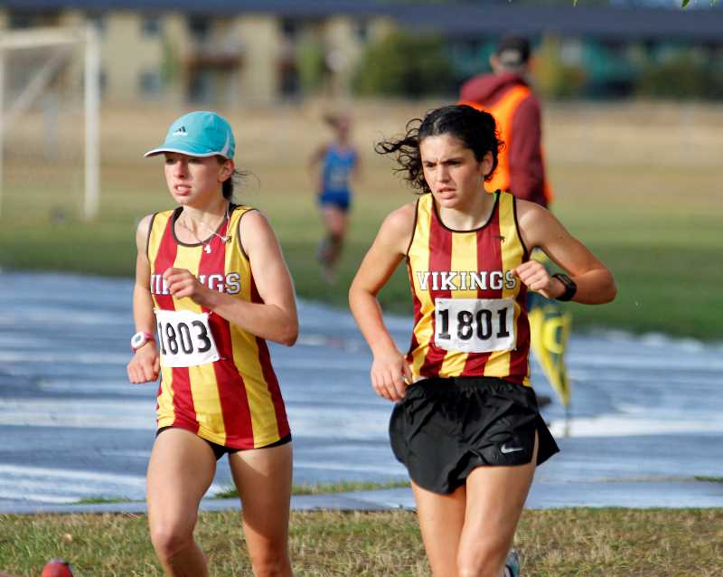 NEWS-TIMES PHOTO: WADE EVANSON - Forest Grove runners Hannah Berdahl (left) and Hannah Aguirre (right) slog through the wet track during their one-two finish at last week's meet versus North Salem and McNary.
