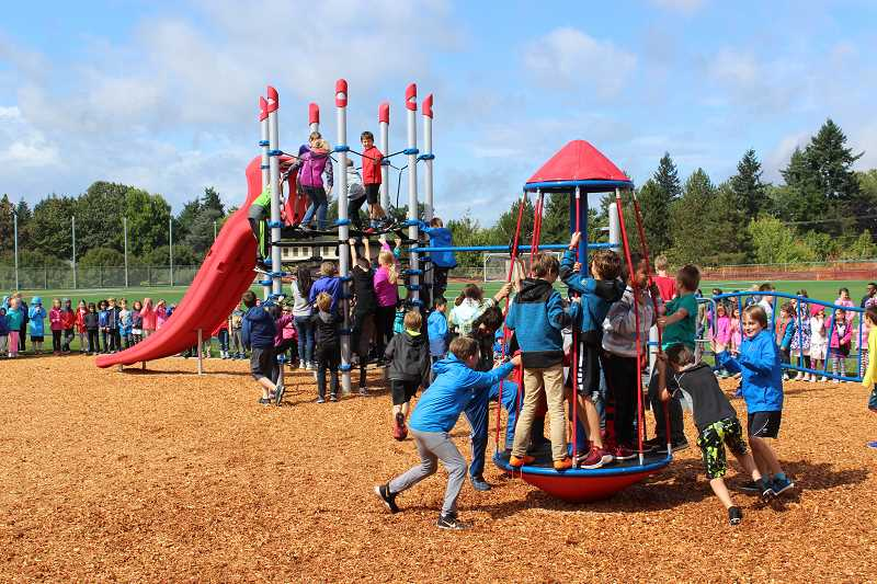 CONNECTION PHOTO: COREY BUCHANAN - Rieke Elementary School students enjoy their new playground moments after the ribbon-cutting ceremony.