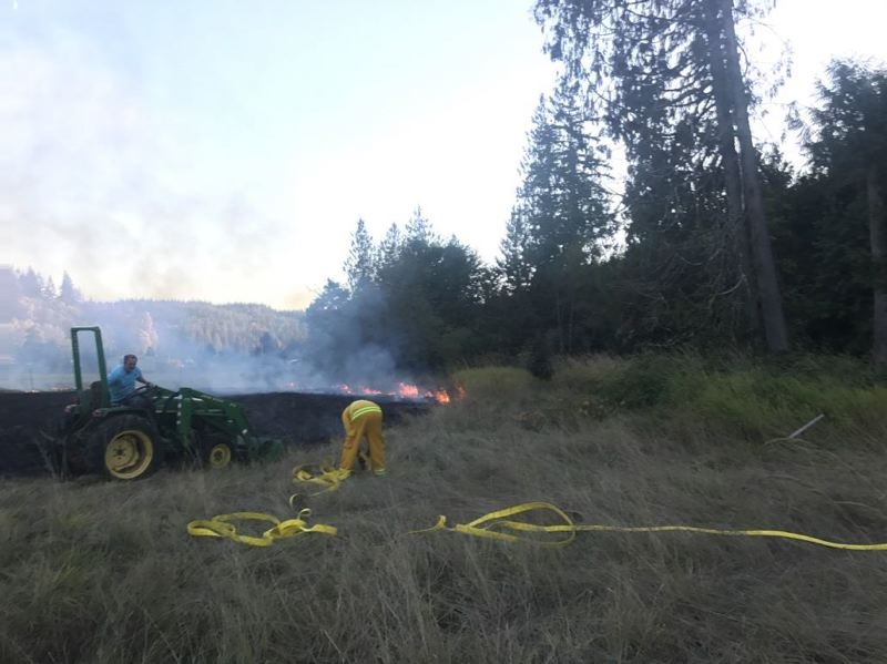 PHOTO COURTESY OF COLUMBIA RIVER FIRE AND RESCUE - Fire crews work to put out a 4.8 acre fire in a cut hayfield on Bishop Creek Road. The fire broke out Tuesday, Sept. 26.