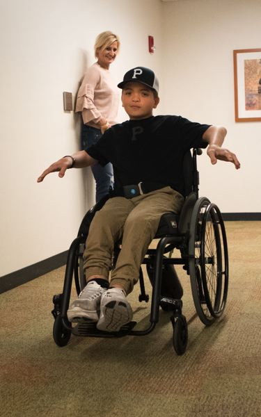 TIMES PHOTO: JAIME VALDEZ - Jake Dering, 12, cruises down a corridor at Shriners Hospital for Children in Portland in his motorized, remote-controllable wheelchair as mother Chellie looks on.