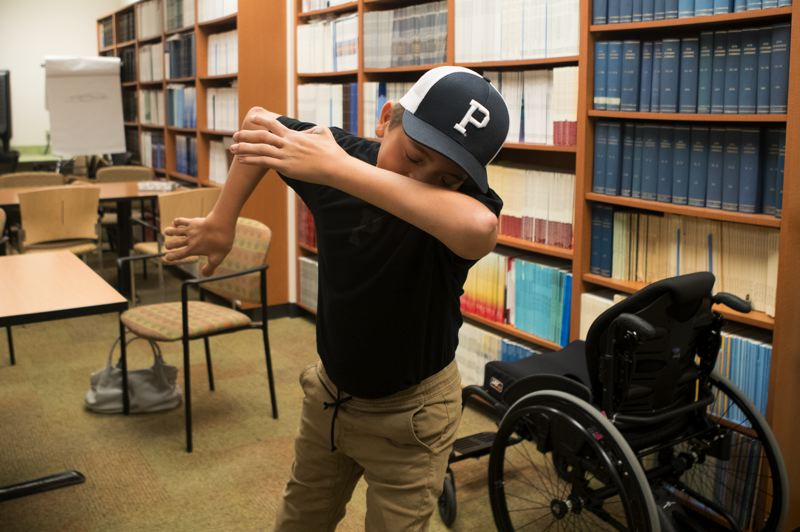 TIMES PHOTO: JAIME VALDEZ - Even with rods in his spine, 12-year-old Jake Dering still has some moves. He's shown here 'dabbing' in the medical library at Shriners Hospital for Children, where he periodically goes for treatment.