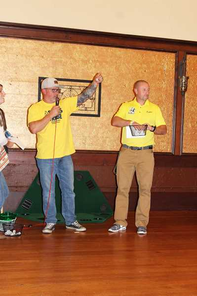 HERALD PHOTO: KRISTEN WOHLERS - Tim Austen and Ryan Oliver hand out raffle prizes at the 'All In Against Childhood Cancer' fundraiser night on Sept. 23.