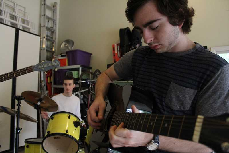 REVIEW PHOTO: SAM STITES - Spencer Schillinger solos during a weekend jam session in the garage at Spencer Brown's (left) house.