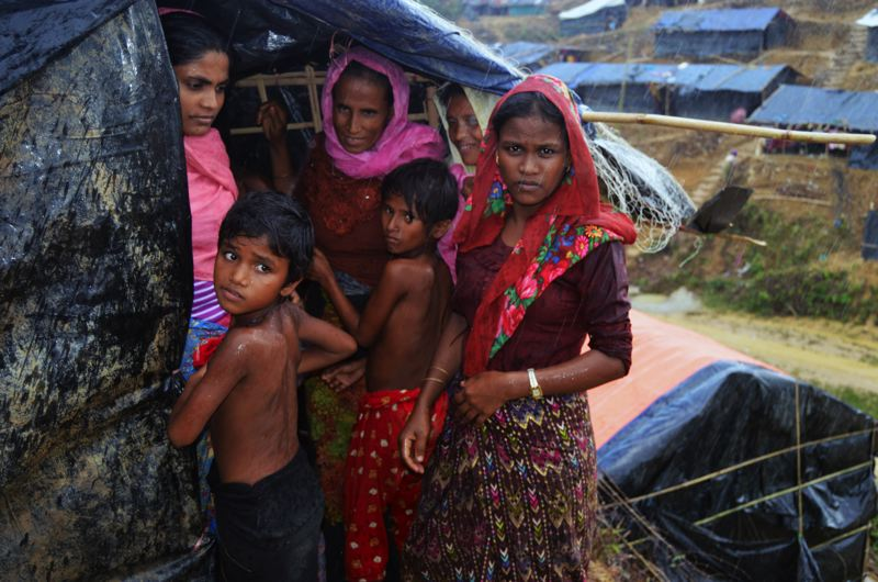 COURTESY OF MEDICAL TEAMS INTERNATIONAL - A Rohingya family huddles beneath a tarp for shelter from the rain in Bangladesh. Estimated hundreds of thousands of Rohingya have crossed the border from Myanmar, fleeing violence, into Bangladesh in recent weeks.