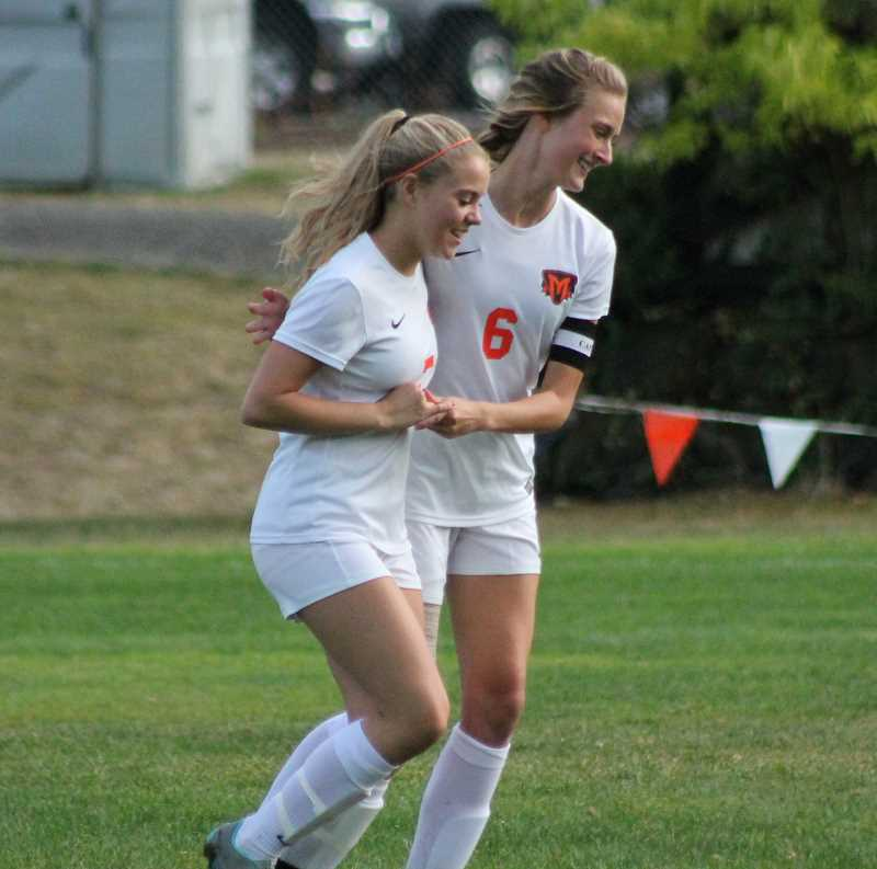 PIONEER PHOTO: CONNER WILLIAMS - Molalla seniors Sierra Cox (left) and Amanda Seward share a congratulatory hug after Cox scored on an assist from Seward during the Indians' 6-0 win over Madras this season.