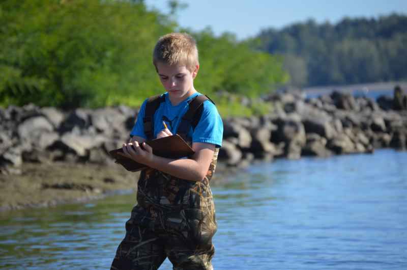 SPOTLIGHT PHOTO: NICOLE THILL - Michael Prince takes careful stock of what he sees in the Columbia River on Wednesday, Sept. 27, during a field study exercise jotting down his observations. Prince is one of many students at Sauvie Island Academy who are conducting their own study of how Dairy Creek and Sturgeon Lake will change over time, while the area is restored by the West Multnomah Soil and Water Conservation District.
