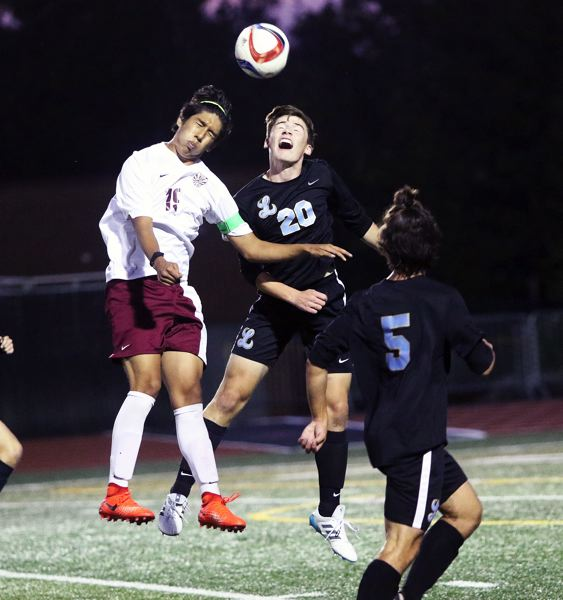DAN BROOD - Tualatin junior Saul Aparicio (left) and Lakeridge senior Nick Bowermaster both go up in an attempt to get a head on the ball during Thursday's match.