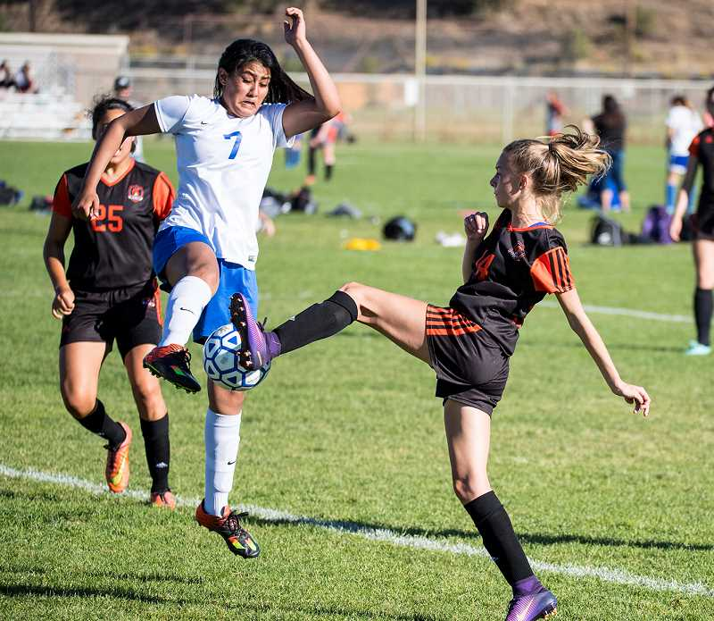 LON AUSTIN/CENTRAL OREGONIAN - Vanessa Martinez, 7, and Lewis both attempt to play the ball at the same time. The Cowgirls are back in action on Tuesday when they travel to Madras to take on the White Buffalos.