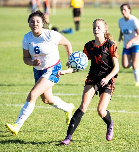 LON AUSTIN/CENTRAL OREGONIAN - Nohemy Zaratte, 6,  plays defense on Gladstone forward Brianna Lewis. Lewis scored four goals in the Gladiators 7-0 victory over the Cowgirls.