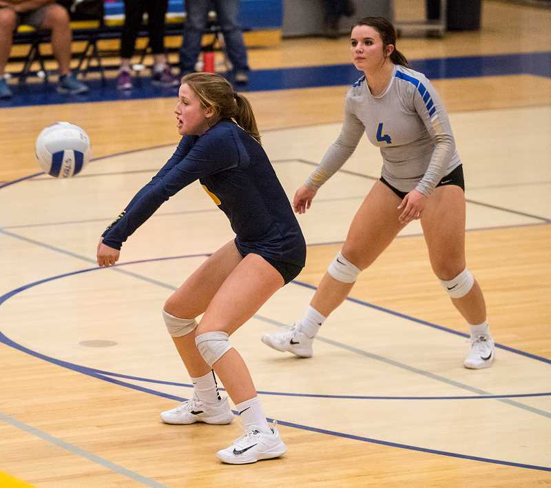 LON AUSTIN/CENTRAL OREGONIAN - Kacie Stafford, a freshman defensive specialist for the Cowgirls, makes a pass during the team's victory over Madras Tuesday night in Prineville. Libero Mekynzie Wells is in the background.