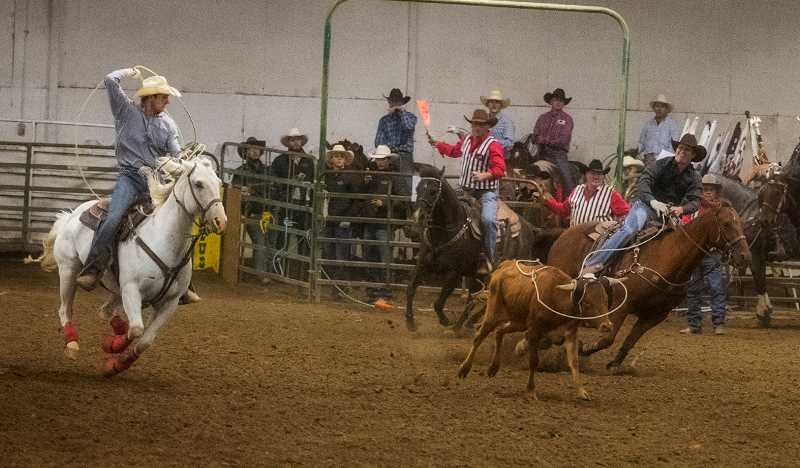 LON AUSTIN/CENTRAL OREGONIAN - Austin (right) and Dayton Stafford make a team roping run at the NPRA finals on Friday. The Prineville brothers placed third in the go round with a time of 6.0 seconds.