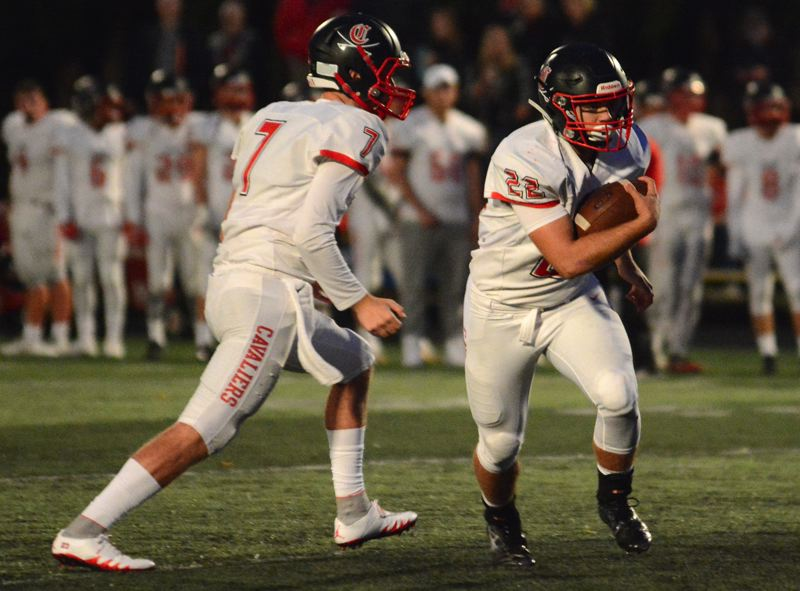 PAMPLIN MEDIA GROUP PHOTO: DAVID BALL - Clackamas running back Nick Vaughn takes the hand off from quarterback Mitchell Modjeski during their team's 49-28 win at Barlow on Friday.