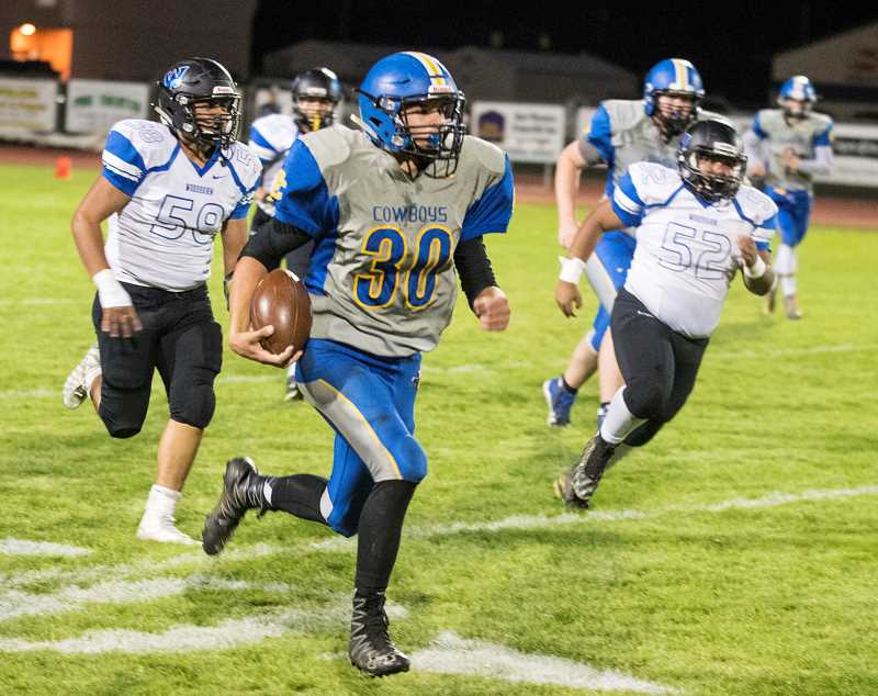 LON AUSTIN/CENTRAL OREGONIAN - Kyle Knudtson runs the ball around the right end for a 39-yard run in the Cowboys 39-0 win over the Woodburn Bulldogs. Knudtson led all players in rushing with 84 yards on 10 carries.