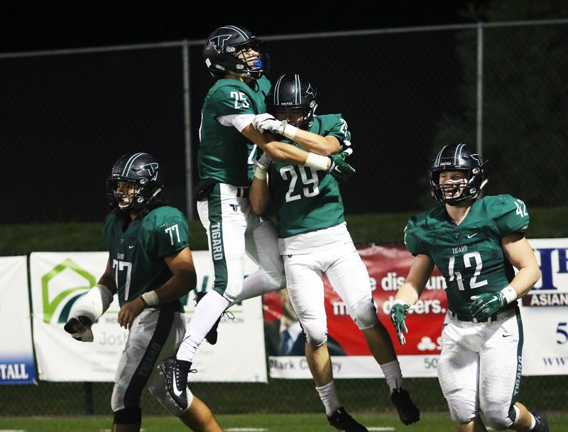 DAN BROOD - Tigard High School seniors Braden Lenzy (25) and Spencer Smith (29), along with Isaia Tavita Porter (77) and Carter Dennis, celebrate after a Smith touchdown run in the 48-19 win over Lakeridge.