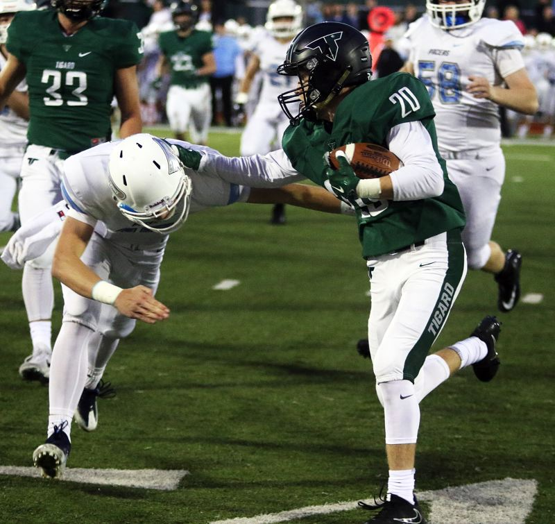 DAN BROOD - Tigard sophomore Tyler Penn (20) looks to get up field after intercepting a Lakeridge pass in Friday's game.