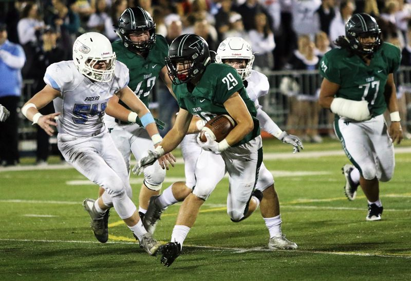 DAN BROOD - Tigard senior Spencer Smith (29) looks to get past Lakeridge senior Hunter Paulson during Friday's game.