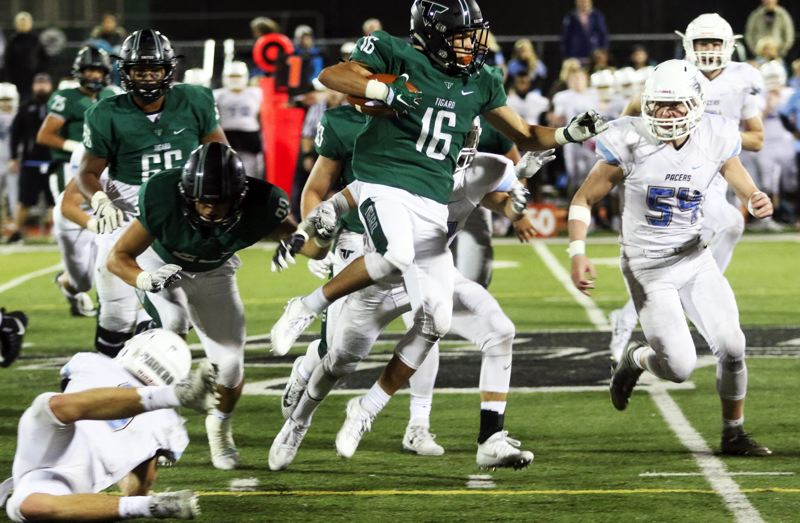 DAN BROOD - Tigard sophomore Max Lenzy (16) takes to the air to gain more yardage on a running play during the win over Lakeridge.