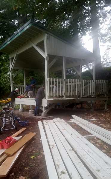 REVIEW PHOTO: GARY M. STEIN - Members of the Lake Oswego Rotary Club replace floorboards on the bandstand in lower George Rogers Park during a work party in late September.