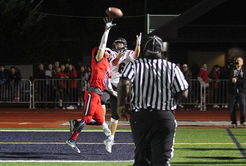 REVIEW PHOTO: MILES VANCE - Lake Oswego's Matt Sebolsky (left) tips the ball away from Jackson Willig on the next-to-last play of the game in the Lakers' 34-27 home win on Friday.