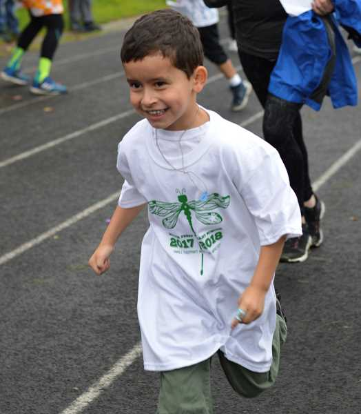 SPOKESMAN PHOTO: CLARA HOWELL - Kindergartener Celestino Soto-Tapia speeds along the track at Boones Ferry.