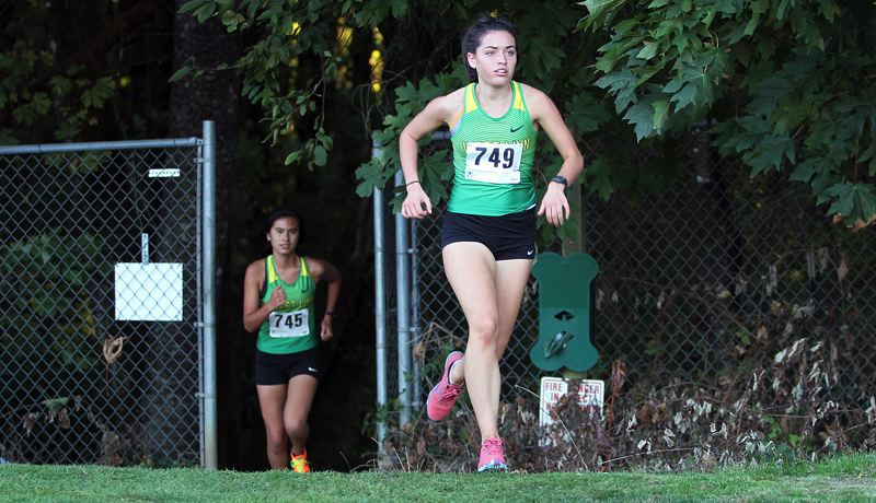 TIDINGS PHOTO: MILES VANCE - West Linn senior Elizabeth Paschall (right) leads sophomore teammate Moya Moses up a hill during their team's meet against Lake Oswego and Sherwood at Lake Oswego Junior High on Sept. 27.