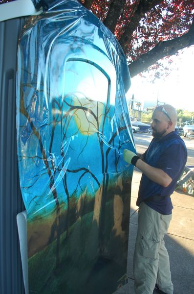 PHOTO BY: RAYMOND RENDLEMAN - On Sept. 27, Andrew Sparre of Service Graphics installs an artistic protective covering on a 24-hour toilet in the Oregon City Municipal Parking Lot.