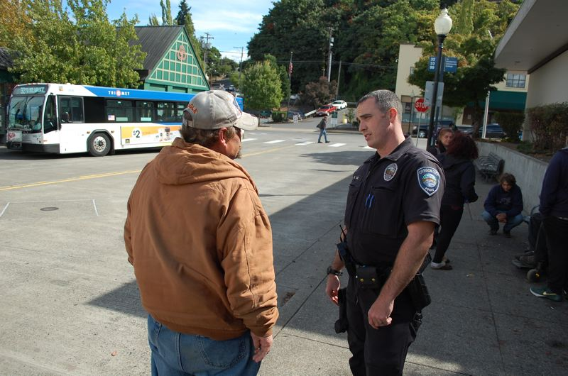 PHOTO BY: RAYMOND RENDLEMAN - Officer Mike Day talks with a client at the Oregon City transit center downtown.