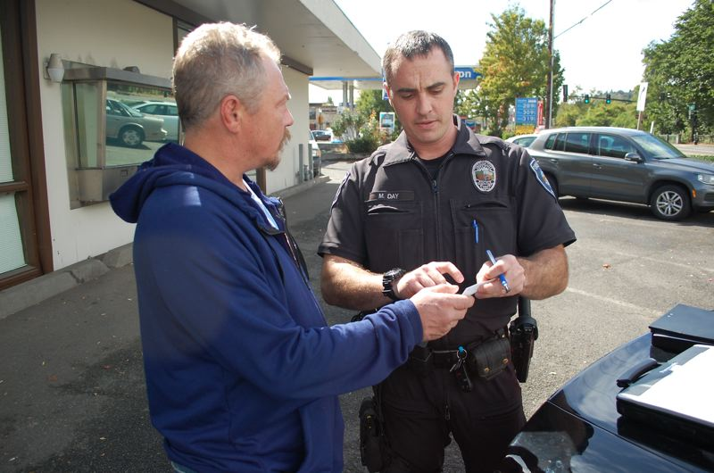 PHOTO BY: RAYMOND RENDLEMAN - Officer Mike Day discusses options for overcoming homelessness with Jason Conroy, 46.