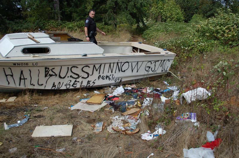 PHOTO BY: RAYMOND RENDLEMAN - Officer Mike Day checks out an abandoned boat that someone had been sleeping in behind the commercial properties on Beavercreek Road.