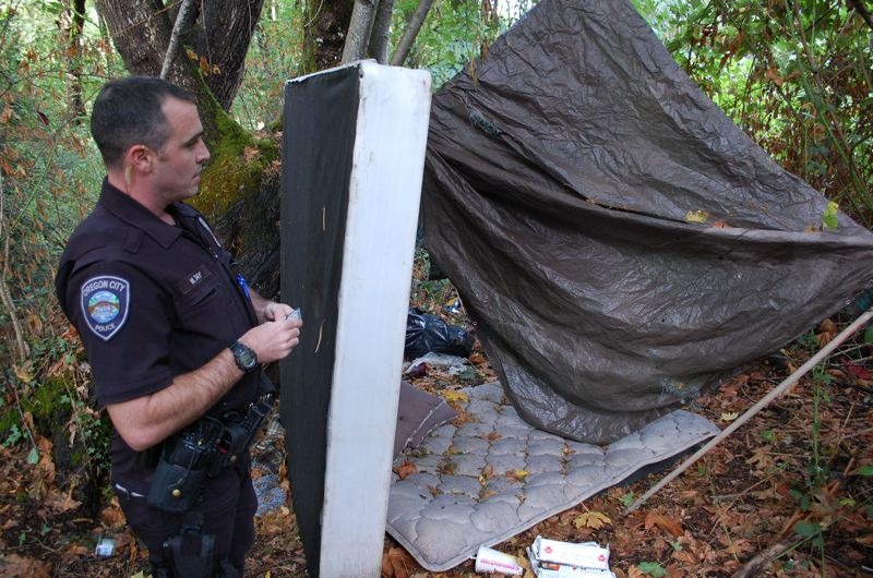 PHOTO BY: RAYMOND RENDLEMAN - OCPD's Mike Day writes 'no camping' on his business card after finding an abandonded mattress in Metro's Newell Creek Canyon natural area.