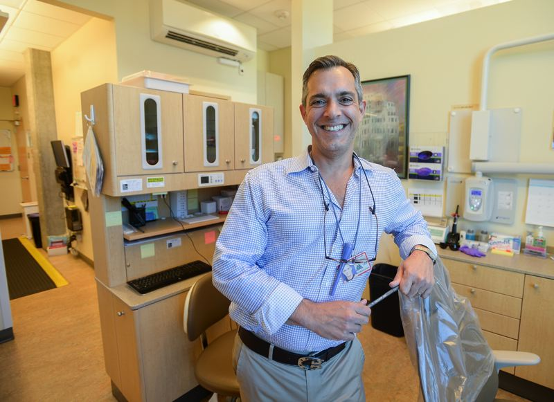 OUTLOOK PHOTO: JOSH KULLA - County Dental Director Dr. Len Barozzini flashes his pearly whites inside a dental clinic at the county's downtown location in Portland.