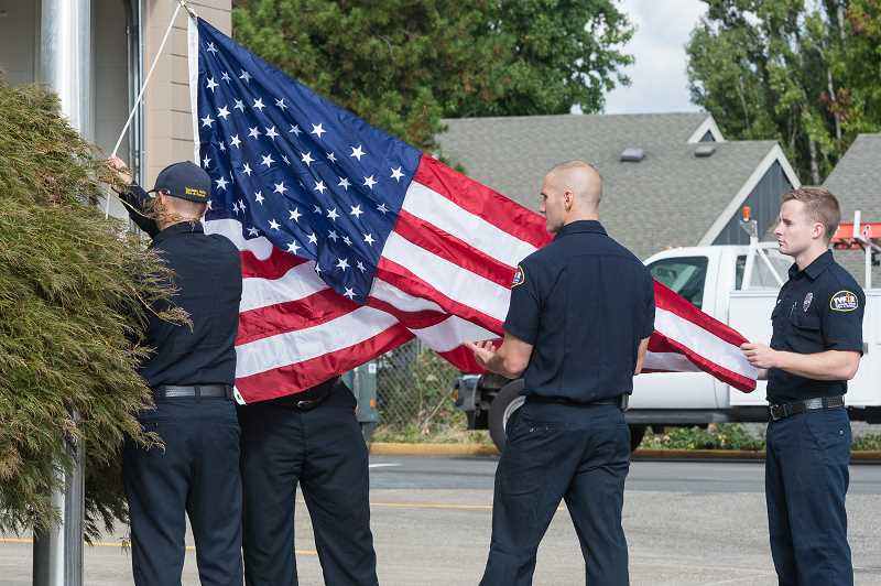 HILLSBORO TRIBUNE PHOTO: CHRISTOPHER OERTELL - Engineeer Chris Tompkins, firefighter Matt Cox and firefighter Galen Cox begin to raise the flag at the remodeled Tualatin Valley Fire and Rescue Station 64.