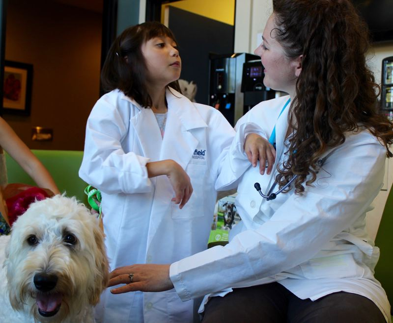 TIMES PHOTO: MANDY FEDER-SAWYER - Hailey Jensen spends some time with her new service dog Rey's veterinarian Kristi Pierce on Wednesday, Sept. 27. Banfield Pet Hospital also gave Hailey her own lab coat.