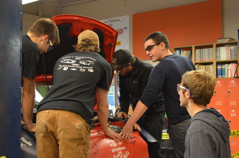 FILE - Students in St. Helens High School's auto-tech class work to diagnose an issue under the hood of a Ford Fiesta in 2015. Automotive technology, home economics, financial literacy and other how-to programs are not as commonplace in American high schools as they once were.