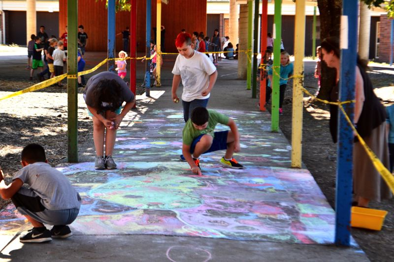 POST PHOTO: BRITTANY ALLEN - Welches' classes decorate the breezeway outside their school with colorful chalk drawings depicting kindness.