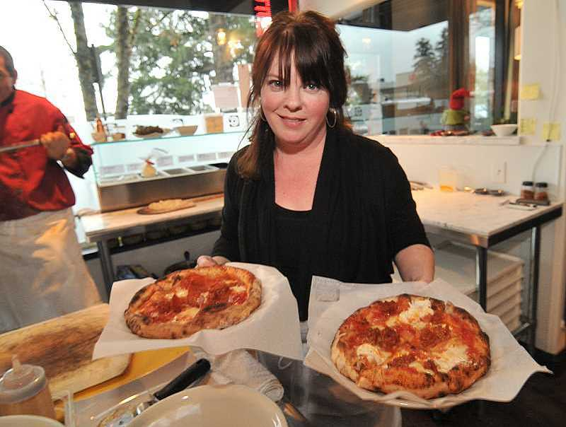 REVIEW FILE PHOTO: VERN UYETAKE - Lisa Shaw-Ryan dishes up pizza at Chuckie Pies. The popular restaurant, now located on Fifth Street in downtown Lake Oswego, will move to The Windward when the mixed-use development is completed in early 2018.