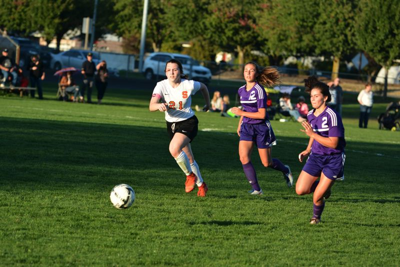 SPOTLIGHT PHOTO: JAKE MCNEAL - Indians junior defender Shayna Redpath (21) races Astoria freshman midfielder Haley Kelley (12) and sophomore midfielder Taleigh Cole (2) to a free ball.