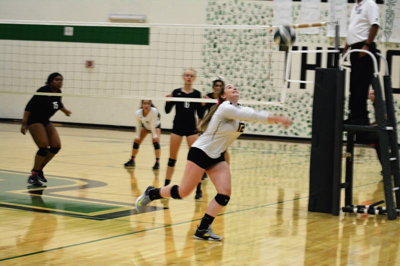 SPOTLIGHT PHOTO: JAKE MCNEAL - Lions senior setter Kenna Reinholdt (12) hustles for a save.