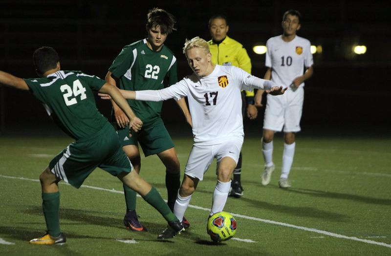 REVIEW/NEWS PHOTO: JIM BESEDA - Milwaukie defender Hunter Shelley keeps the ball away from Putnam's Steve Sanchez (24) and Gabe Dyer (22) during the second half of Tuesday's Northwest Oregon Conference boys' soccer game.
