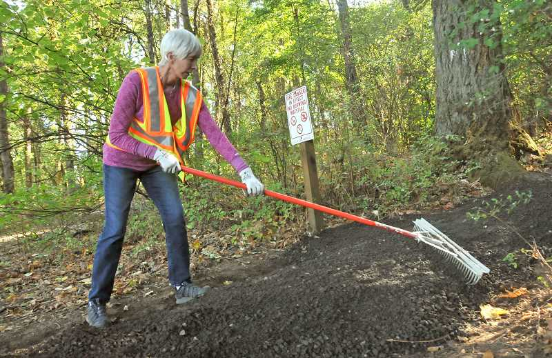 REVIEW PHOTO: VERN UYETAKE - Barbara Fisher rakes out some new gravel on one of the paths that meander through Freepons Park during a Friends of  Hallinan Heights Woods work party in late September.