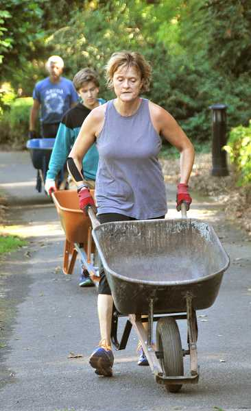REVIEW PHOTO: VERN UYETAKE - Nancy Moon Eilers returns for another load of gravel during a stewardship work party at Freepons Park last month.