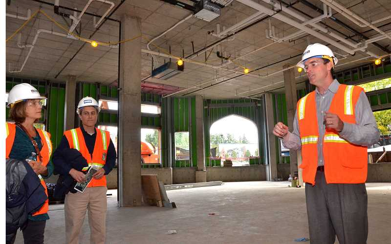 REVIEW PHOTO: VERN UYETAKE - Developer Patrick Kessi (right) leads a tour of one of the ground-floor retail spaces in The Windward, a mixed-use development under construction in downtown Lake Oswego. When finished in early 2018, the project's three buildings will include 200 apartments and 24,000 square feet of commercial space.