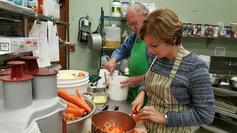 SUBMITTED PHOTO: MARIA BIGELOW - John Fowlks and Gayle Stickley help prep food for meals at the Lake Oswego Adult Community Center, where the city's Meals on Wheels program is based.