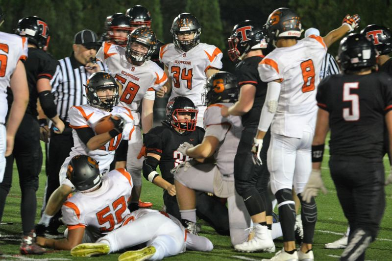 SPOTLIGHT PHOTO: JAKE MCNEAL - Indians senior defensive back Nicky Gill (20), senior lineman Nate Maller (58), junior linebacker Matt Roth (34) and senior defensive back Tevin Jeannis (8) appeal to the refs for a fumble recovery against Tillamook.