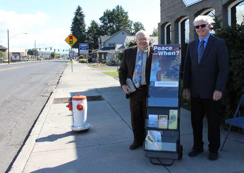 HOLLY SCHOLZ/CENTRAL OREGONIAN  - Bill Schleicher, left, and Rick Burhart, who have been members of the Jehovah's Witnesses faith for many years, have begun participating in a new public ministry that invites people to take Bible literature from a cart.
