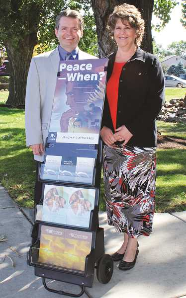 HOLLY SCHOLZ/CENTRAL OREGONIAN   - Casey and Tammie Cardin, members of the Prineville Kingdom Hall of Jehovah's Witnesses, offer Bible literature to the community at Pioneer Park using the new cart public ministry.